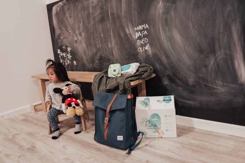 14 Amazing Activities for Dads and Kids by top US lifestyle blog, Sylvie in the Skye: image of a little girl holding a Mickey Mouse doll in front of a chalkboard with writing on it, and a wooden bench with a polaroid instax camera, pampers diaper wipes, green jacket, blue diaper bag, and box of Pampers Pure Protection diapers on it.