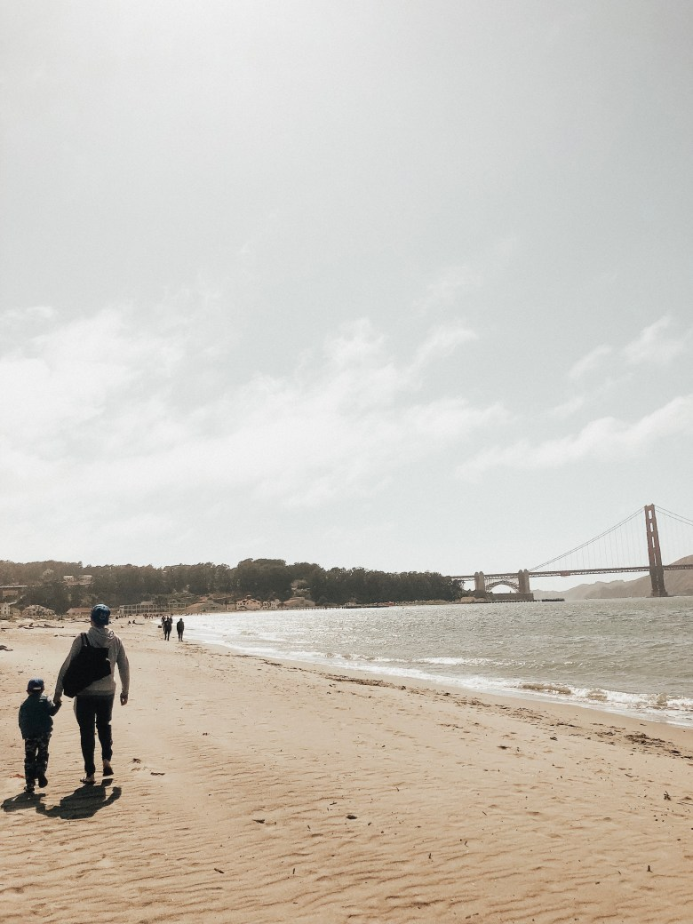14 Amazing Activities for Dads and Kids by top US lifestyle blog, Sylvie in the Skye: image of man and young boy holding hands and walking down a sandy beach toward the Golden Gate Bridge.