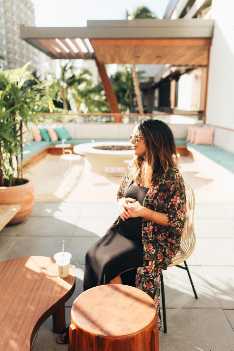 44 BEST MATERNITY SUMMER DRESSES FOR TRAVEL & WEEKENDS by popular San Francisco blog, Sylvie in the Sky: image of a woman sitting outside and wearing a black maxi maternity dress and floral kimono.