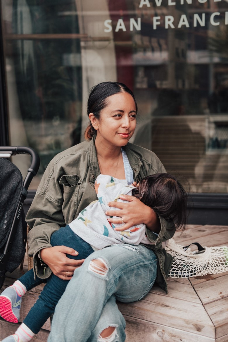 The Best Breastfeeding Essentials by popular California mommy blog, Sylvie in the Sky: image of a woman sitting outside and breastfeeding her child.