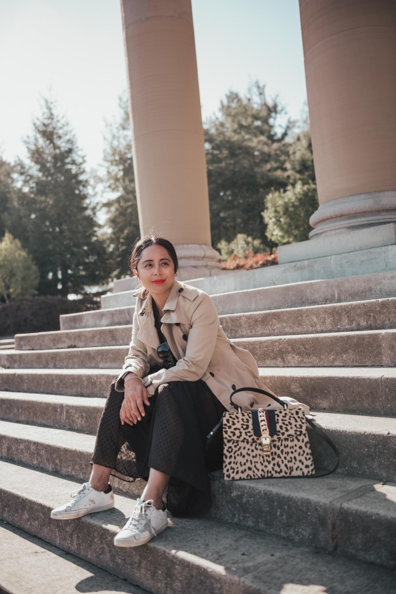 Women's Trench Coats and Outfit Inspiration by popular San Francisco fashion blog, Sylvie in the Sky: image of a woman sitting on some steps outside and wearing a Topshop khaki Staple Trench Coat.