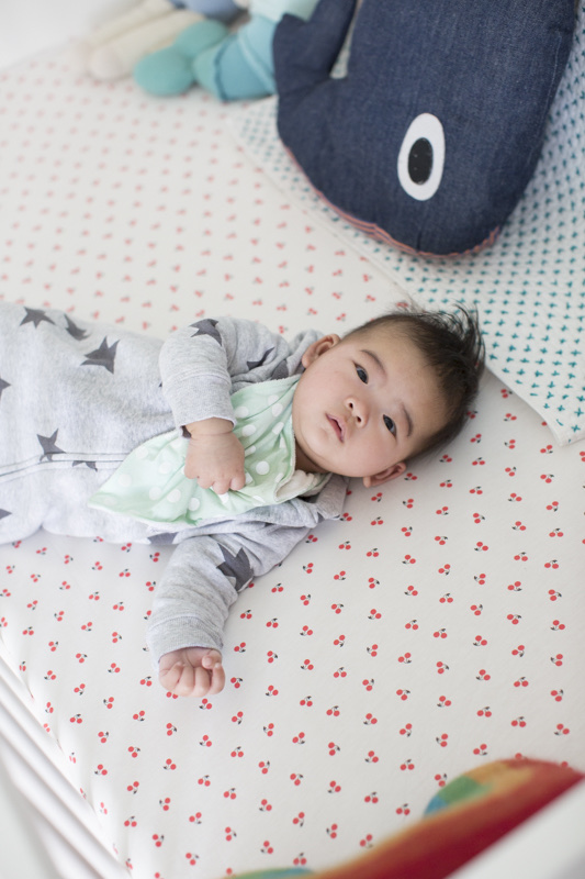 11 Best Gender Neutral Nursery Baby Products by popular San Francisco life and style blog, Sylvie in the Sky: image of baby laying in a white crib.