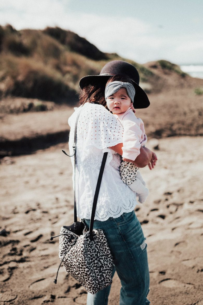 12 Affirmations for Mothers & Mom Guilt by popular San Francisco life and style blog, Sylvie in the Sky: image of a mom holding her baby at the beach.