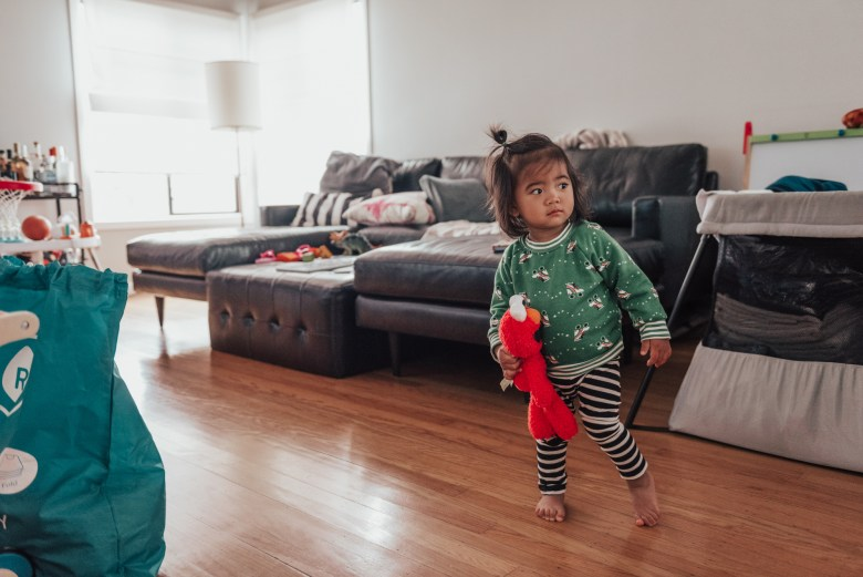 10 Best Baby Proofing Products for Every Home by popular San Francisco mom blog, Sylvie in the Sky: image of a toddler age girl holding a Elmo doll.