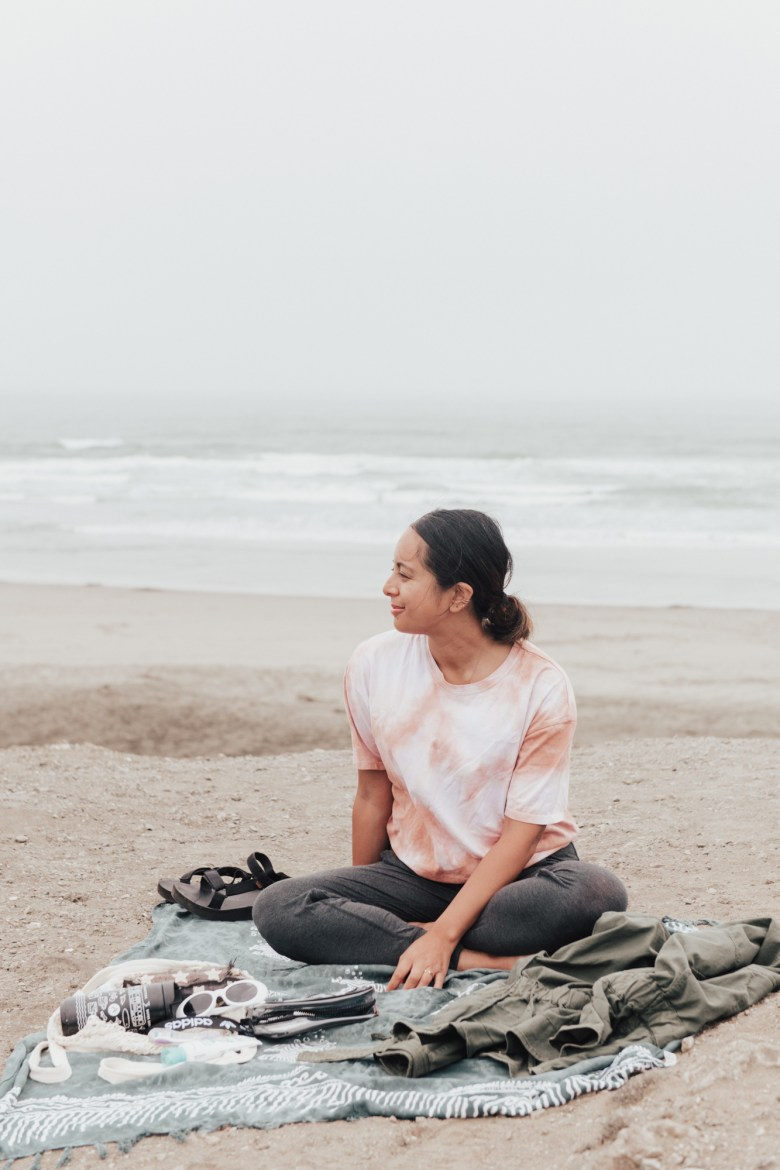 Breathwork Meditation by popular San Francisco lifestyle blog, Sylvie in the Sky: image of a woman wearing a tie dye shirt and meditating on a beach.