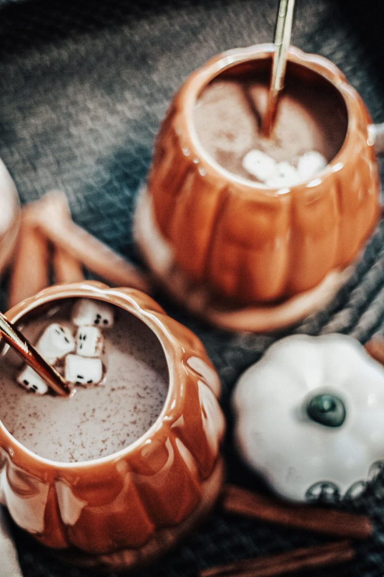 At Home Halloween by popular San Francisco motherhood blog, Sylvie in the Sky: image of pumpkin mugs filled with hot chocolate and ghost marshmallows.