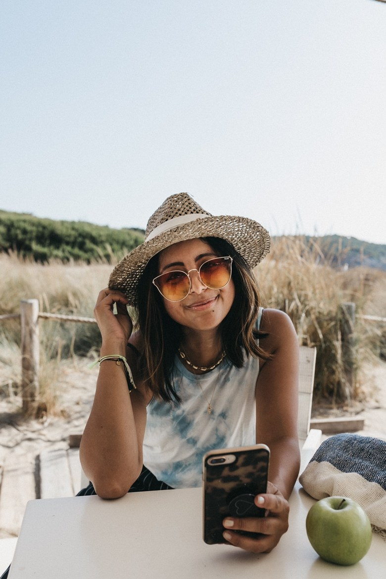Online Therapy by popular San Francisco lifestyle blog, Sylvie in the Sky: image of a woman sitting outside at the beach and looking at her smartphone.