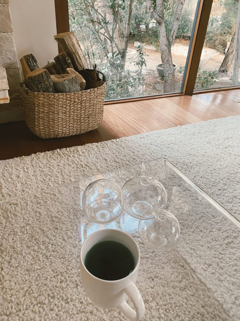 Chlorophyll Water by popular San Francisco lifestyle blog, Sylvie in the Sky: image of mug filled with Chlorophyll water on a acrylic coffee table.