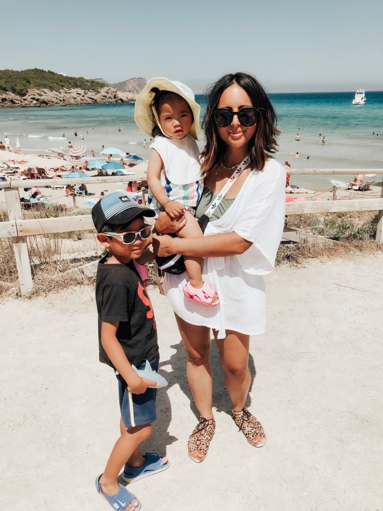Natural Sunscreen for Babies by popular San Francisco motherhood blog, Sylvie in the Sky: image of a mom holding her baby daughter and standing next to her young son at the beach.