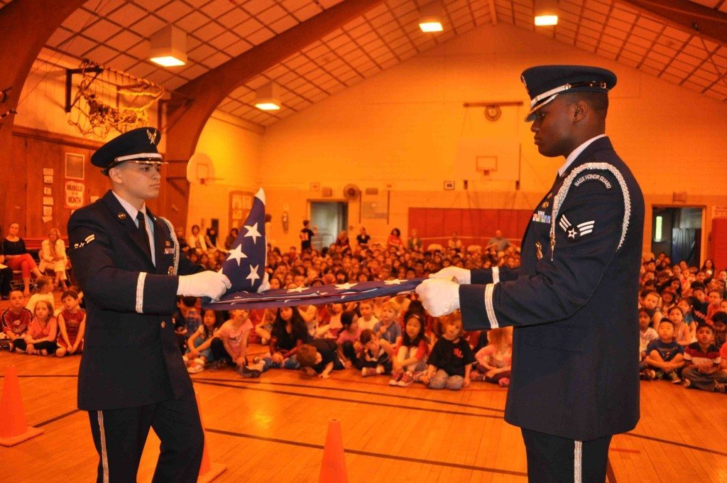 Airman First Class Michael D'Ancona and Senior Airman Assad Pharr demonstrated how to properly fold an American flag during a special visit to Robbins Lane Elementary School in Syosset on May 23. (Syosset-Jericho Tribune, June 19, 2014; photo added here October 2014)