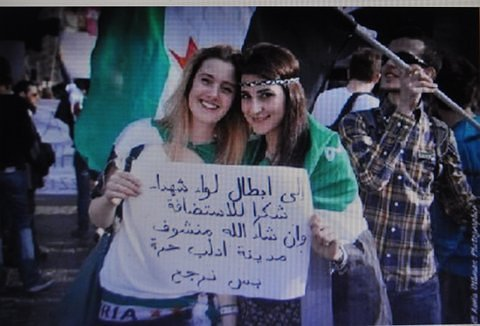 "Rome. Odalisques hold Arabic sign: ""To the heroes of Iiwa Shuhada, thanks for the hospitality and God willing we will see the city of Idlib free when we return."""