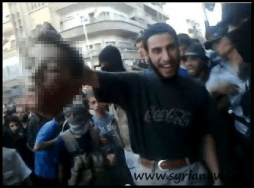 image-The picture is full of irony: The severed head is shown to the crowd by a Wahhabi terrorist who is wearing a Coca-Cola shirt. Coca-Cola, the symbol for western freedom.