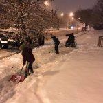 Niños se detienen para ayudar a un hombre en silla de ruedas en la nieve