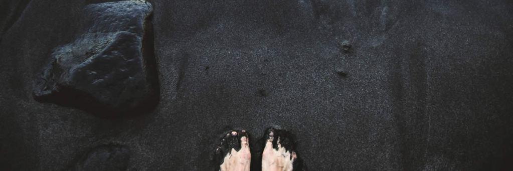 Pé na areia preta molhada