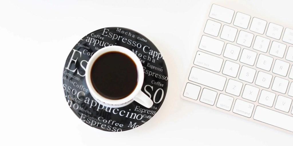 Xícara de café com teclado ao lado