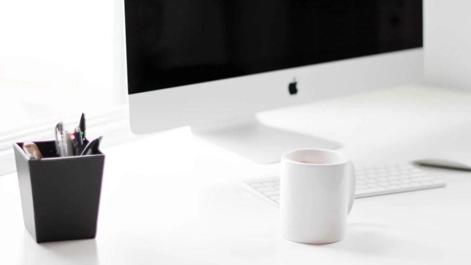 Mesa com iMac, caneca e teclado