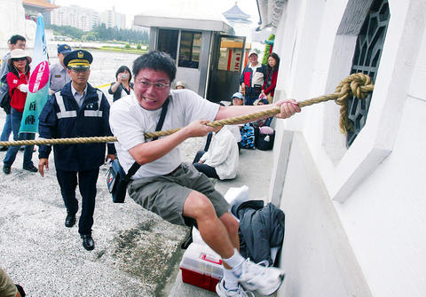A member of the 908 Taiwan Republic Campaign yesterday tries to pull the bars from a window in the wall surrounding the National Taiwan Democracy Memorial Hall during an event the campaign called ``Tear down the feudal wall and open up a democratic space. The event coincided with the ceremony changing the halls name from Chiang Kai-shek Memorial Hall.