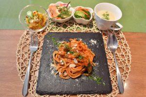 テーブルの上のトマトパスタと前菜、スープの写真