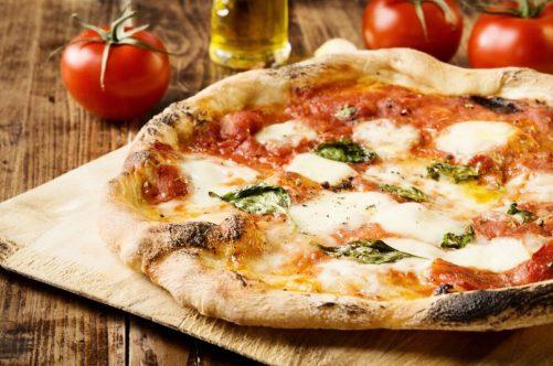 焼き上がってテーブルに置かれたマルゲリータピザ