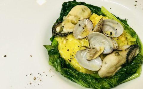お皿に盛られた玄米で作る牡蠣と浅利でミラノ風リゾット