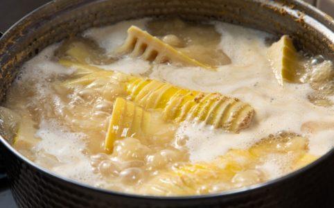 鍋にタケノコとお湯、米糠を入れてアク抜きをする様子