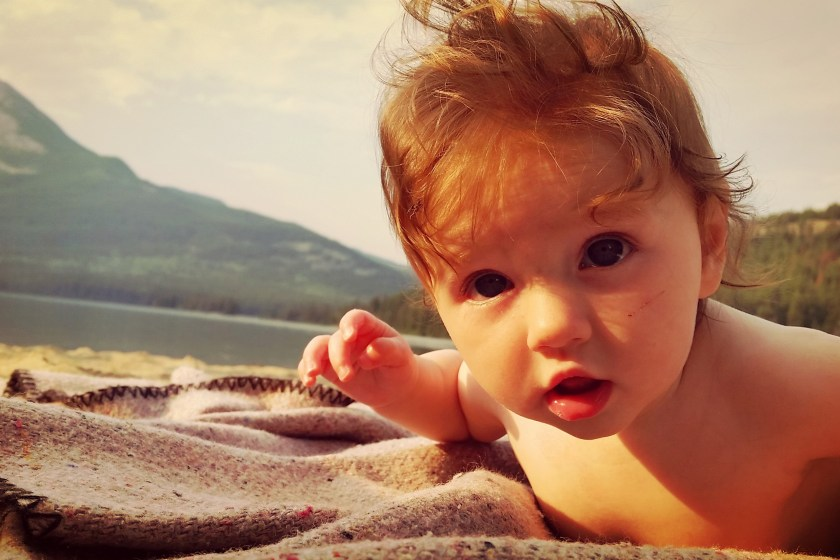 naked baby outside on the beach