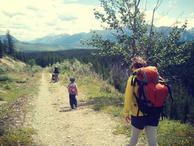 a family bakpacking with kids on a hiking trail carrying large packs and pushing a chariot