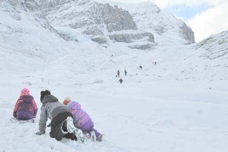 kids crawling through the snow, mountains and glaciers in the background