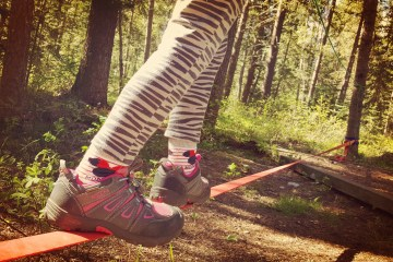 child's feet walking on a tight rope / slackline