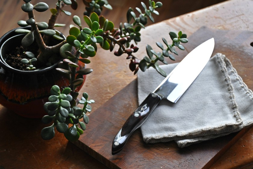 a chopping knife sitting on a cutting board and linen napkin with a jade succulent along side