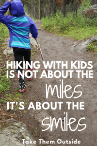 Girl with a stick walking on a muddy path, text reads hiking with kids is not about the miles it's about the smiles