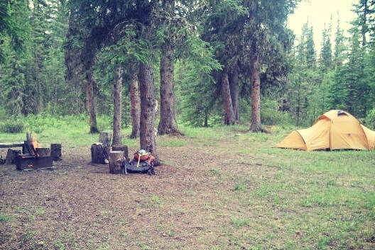 a forested campsite with an orange tent, campfire, and backpack