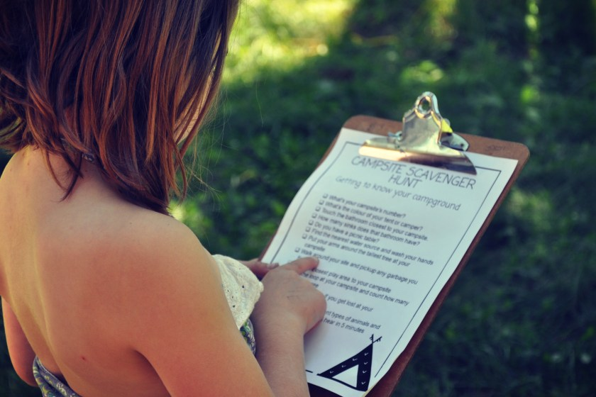 young girl outside looks at a campsite scavenger hunt on a clipboard