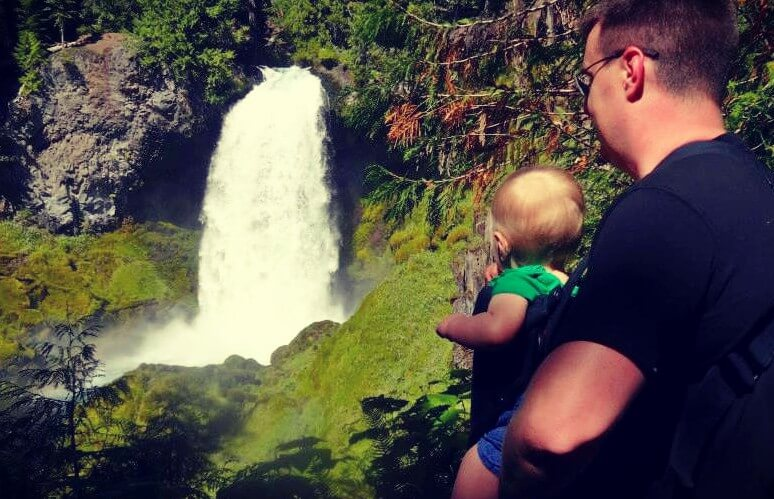 A man holding an infant overlooking a waterfall