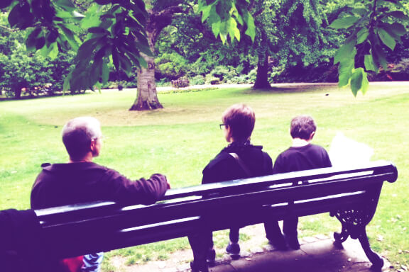 a family sitting on a wooden park bench in a public park