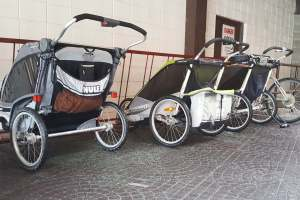 Three all-terrain strollers (Chariots) parked outside a brick building