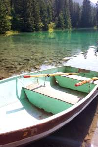 an empty row boat on the shore of a turquoise lake, at valley of the five lakes in Jasper National Park