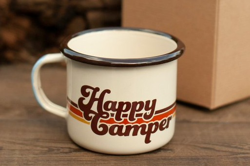 a vintage looking enamel camping mug which reads Happy Camper