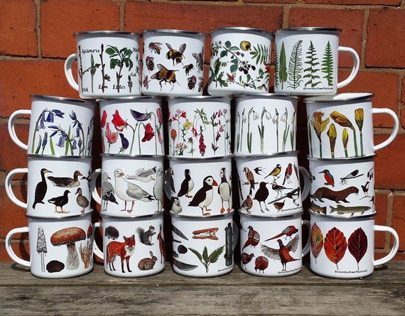 A variety of enamel mugs all printed with different plants and animals.