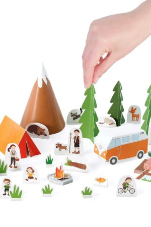 A hand placing a tree in a paper camping set