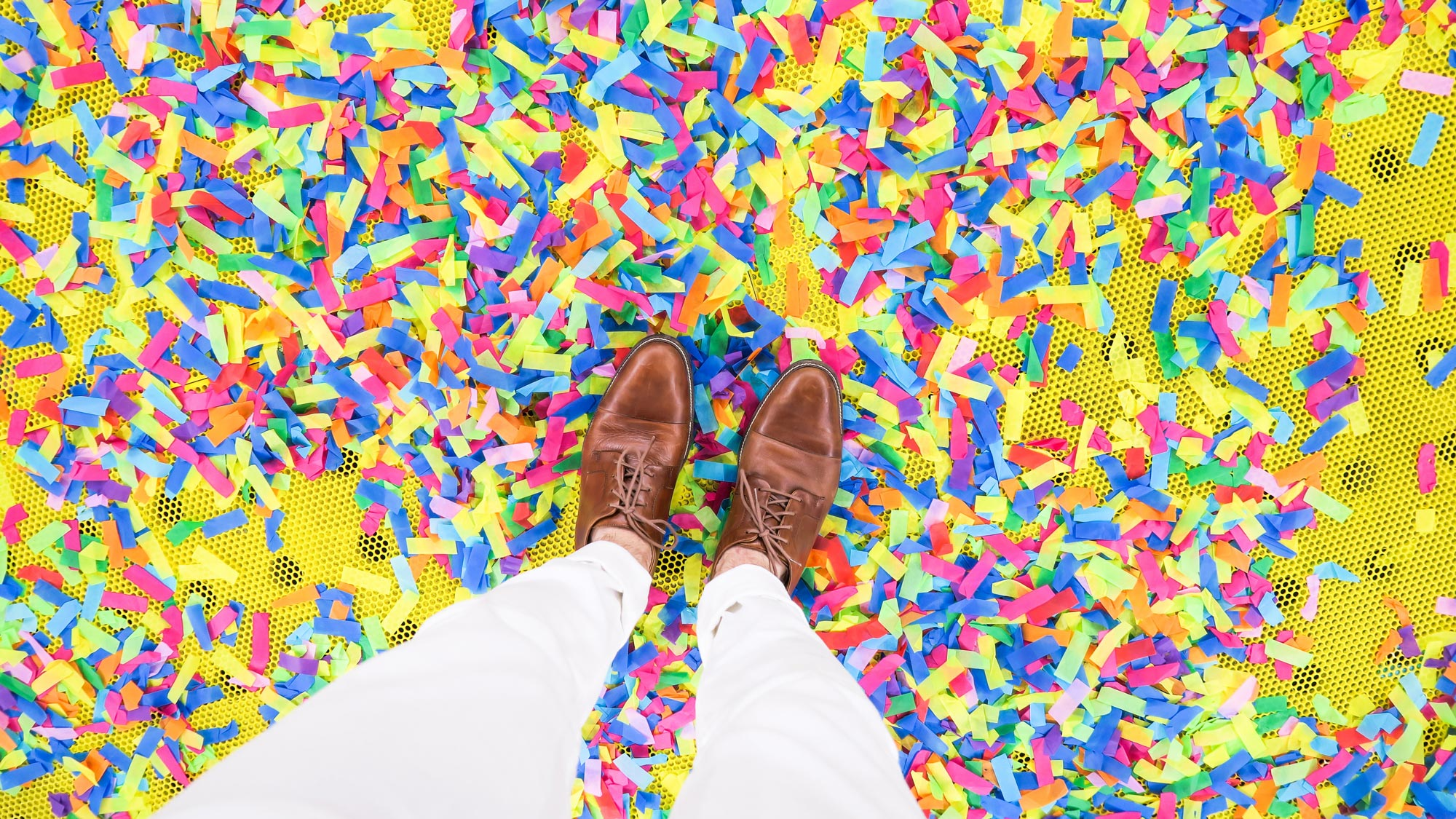 Looking down at white pants covered legs and brown wingtips on an awesome and bright confetti-strewn floor