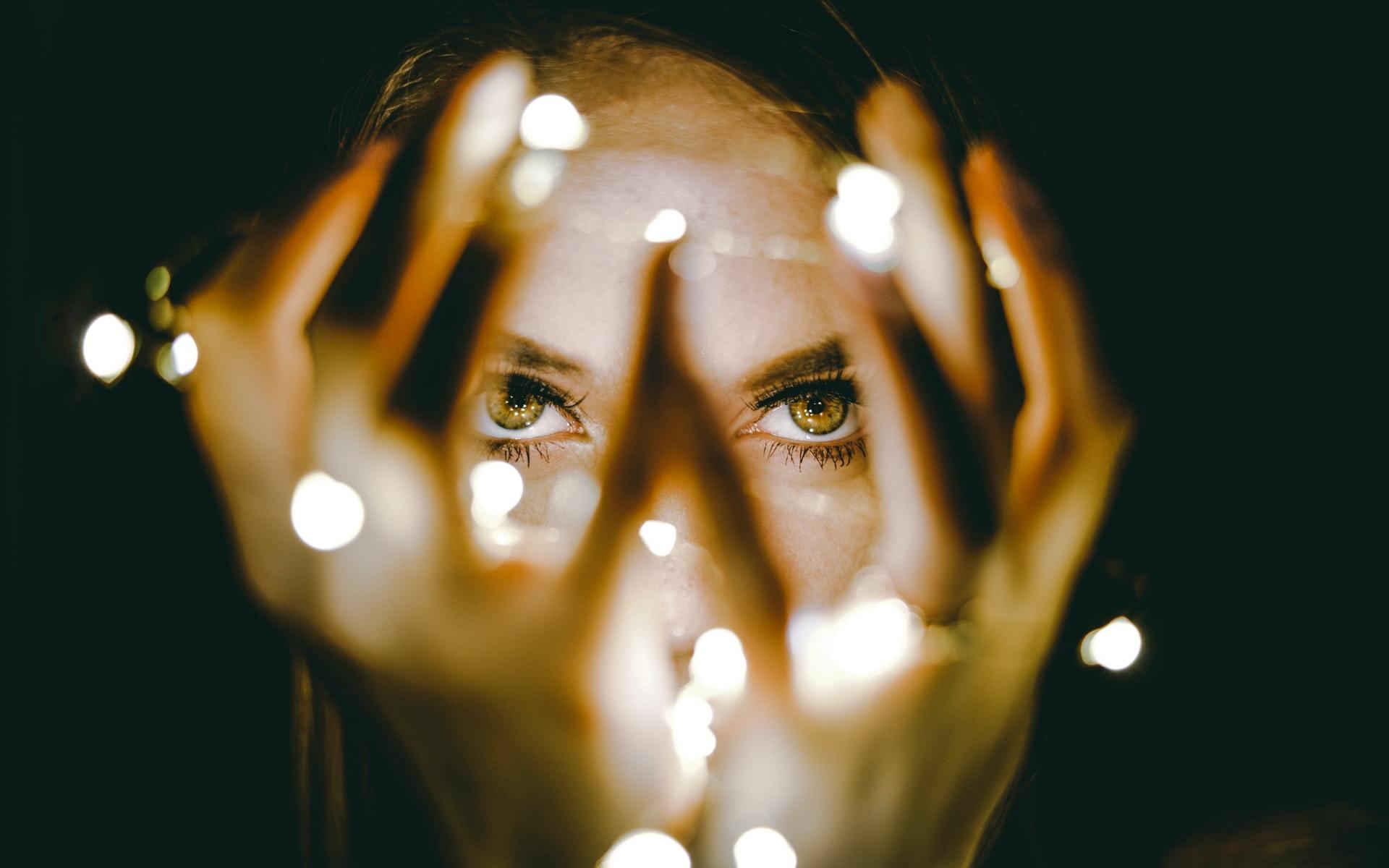 Woman holding fairy lights by Rhett Wesley on Unsplash
