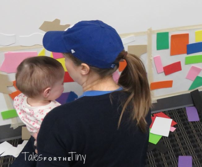 Busy Babies at the Library - Caregiver and baby work on those fine motor skills by placing foam shapes on the contact paper wall - talesforthetiny.com