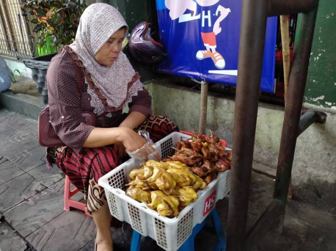 Woman selling grilled birds on the corner outside of Beringharjo market