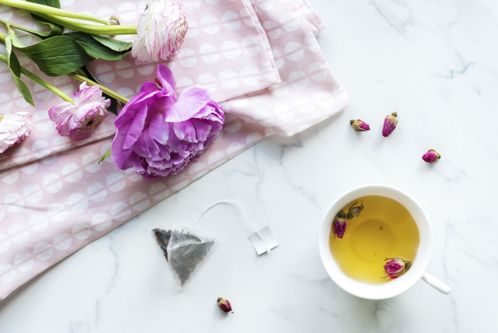 A cup of fruit tea on a marble background beside a cool-toned, soft pink flower
