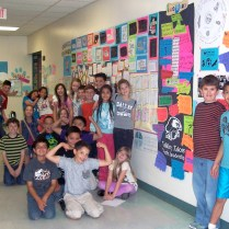 Kids pose with the work they produced during a TTYL program.
