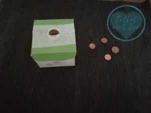 Hucha elaborada con una caja de cartón que contenía una crema hidratante junto a 5 monedas de céntimos de euro