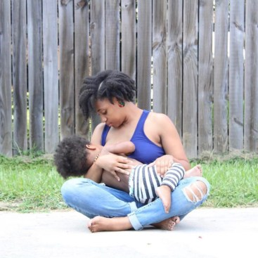 Black mom with blue tank top and ripped jeans holding a toddler to her breast to breastfeed