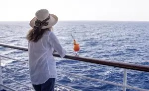 woman drinking and looking at the sea royal albatross