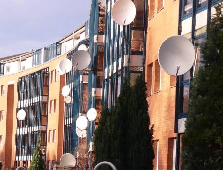 Balkone mit massenhaft angebrachten Sattelitenschüsseln